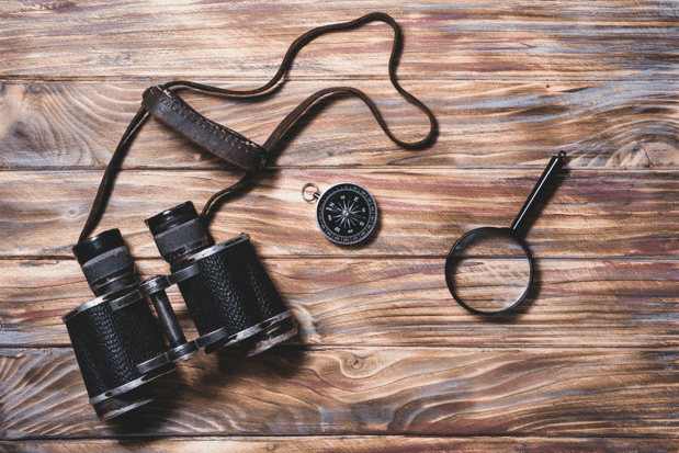 Image of binoculars, magnifying glass, and compass on a wooden table.